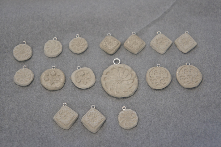 A batch of fine silver clay pieces with eyelets