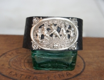 Leather cuff with silver brooch adornment